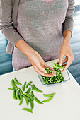 Woman peeling green peas in the kitchen