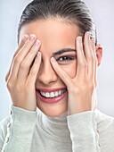 Young woman covering face with hands