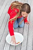 High angle view of a girl touching a fish in a bowl