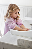 Cute little girl washing hands in bathroom sink