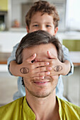Boy covering his father's eyes