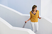 Woman using mobile phone while walking down stairs