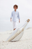 Blurred boy walking towards bottle with note inside on beach