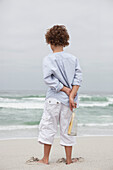 Rear view of a boy holding bottle with message on the beach