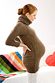 Side profile of a pregnant young woman standing and looking at her abdomen