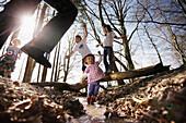Children playing along the lakeshore, jumping over a stream, Leoni castle grounds, Leoni, Berg, Lake Starnberg, Bavaria, Germany
