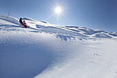 Two girls, 12 and 2 years, on a sledge, Kloesterle, Arlberg, Tyrol, Austria