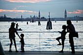 Family at the pier in Lido di Venezia, View towards Venice, Veneto, Italy