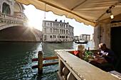Elderly couiple enjoying a meal at the Rialto bridge, Venice, Veneto, Italy