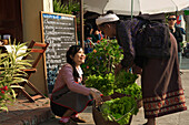 Young woman buying salat from elderly lady for a restaurant, Luang Prabang, Laos