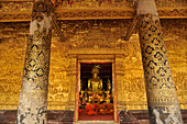 Gallery with golden relief and monks at evening prayer, Wat Mai Suwannaphumaham, Luang Prabang, Laos, Lao Peoples Democratic Republic