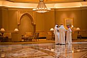 Four Arabian men inside atrium of Emirates Palace hotel, Abu Dhabi, United Arab Emirates