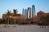 Sandy beach with palms, Emirates Palace hotel and high rise buildings, Abu Dhabi, United Arab Emirates