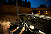 Young woman driving in a convertible car at night, Stuttgart, Baden Wurttemberg, Germany