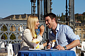 Young couple eating ice cream in a cafe on Schlossplatz, New Castle, Stuttgart, Baden Wurttemberg, Germany