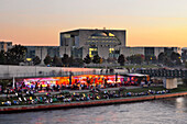 Capital beach cafe at the banks of river Spree, new federal chancellery at dusk, Berlin, Germany, Europe