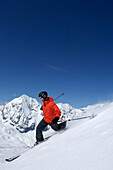 Skier skiing with full winter equipment, Koenigspitze, Ortler Alps, South Tyrol, Trentino-Alto Adige, Italy