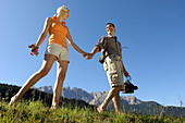 Young couple walking barefoot on the meadow, South Tyrol, Trentino-Alto Adige, Italy