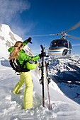 Skier and helicopter on snowy mountain, Alto Adige, South Tyrol, Italy, Europe