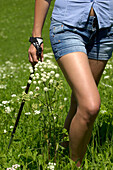 Young woman with hiking poles in a meadow, Alto Adige, South Tyrol, Italy, Europe