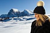 Lächenlde Frau vor verschneiter Berglandschaft, Seiser Alm, Alto Adige, Südtirol, Italien, Europa