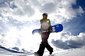 Young woman with snowboard under clouded sky, Alpe di Siusi, Alto Adige, South Tyrol, Italy, Europe