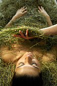 Young woman taking a hay bath, Alto Adige, South Tyrol, Italy, Europe