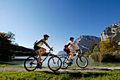 Mountainbiker at the shore of a lake in the sunlight, Alto Adige, South Tyrol, Italy, Europe