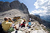 Hikers taking a rest at Santnerpass in the sunlight, Dolomites, South Tyrol, Alto Adige, Italy, Europe