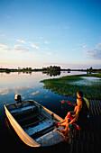 Couple sitting on pier beside boat in Yellow Water wetlands, Cooinda, Kakadu National Park, Australia
