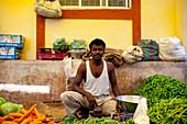 A Vendor Sits Amongst His Fresh Vegetable Produce, Chaudi Market, Chaudi, Goa, India.