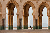 Woman walking past arches of the Hassan II mosque, Casablanca, Morocco
