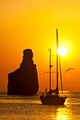 Yacht & strange shaped rock off Benirras beach at dusk, Ibiza, Spain