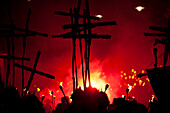 Silhouettes of 17 crosses  lit by red flares on the United Grand Procession, Lewes, East Sussex, England.  Seventeen crosses are carried to commemorate the 17 protestant martyrs killed on Lewes Hight Street between 1555 and 1557.