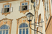 A black cat looks out of an open window in traditional building, Salzburg, Austria