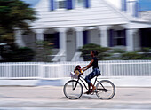 Woman riding bike along Bay Street, Dunmore Town, Harbour Island, Bahamas