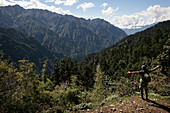 Backpacker with outstretched arms looks over a Himalayan scene, Laya, North West Bhutan