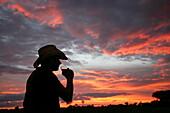 Man enjoying a drink at sunset, Okavango Delta, Botswana