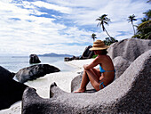 Woman sitting on rocks on the beach, Andse Source D'Argent, La Digue, Seychelles