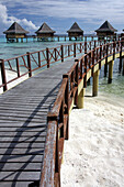 Walkway to holiday huts over lagoon, Rangiroa, French Polynesia