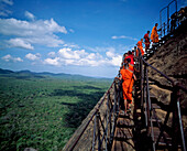 Buddhist monks climbing steps of Sigiriya Lion Rock Fortress, Sigiriya, North Central Province, Sri Lanka