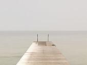 Wooden pier on misty lake at dawn, Sweden