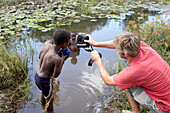 Photographer taking photos of children in river, Tanzania