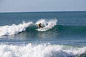 Surfer on big wave, Tanzania