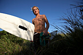 Blond surfer in grass holding surfboard, low angle view, Tanzania