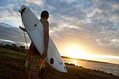 Man holding surfboard at sunset, Tanzania