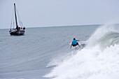 Surfer riding wave with sailboat behind, Tanzania