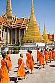 Young monks at Wat Phra Kaeo walking towards Royal Pantheon, Bangkok, Thailand