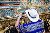 Man taking pictures of bot walls of Wat Phra Kaeo at Grand Palace, Bangkok, Thailand