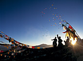 Pilgrims at dawn on hill beside prayer flags throwing windhorses into the air above Ganden Monastery for New Year, Tibet